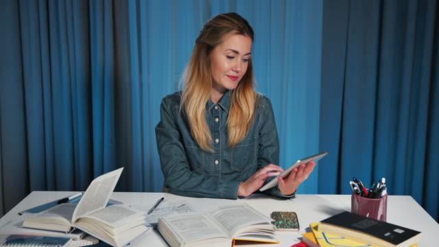 mutlu kız öğrenci bir kot gömlek bir tablet kullanır. sonra arkasını kamera ve gülümsüyor. portre - çalışma kitabı stok videoları ve detay görüntü çekimi