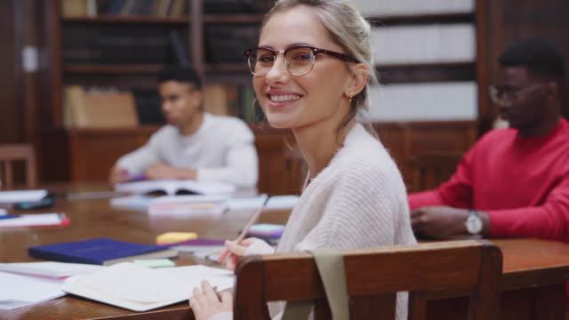 glückliche studentin in der bibliothek - vorlesungsfrei stock-videos und b-roll-filmmaterial