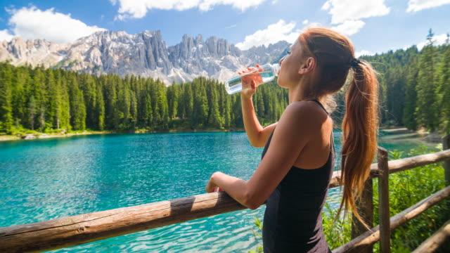 Glücklich weibliche Touristen am Bergsee Lago di Carezza in Dolomiten genießen atemberaubende Aussicht, Trinkwasser – Video