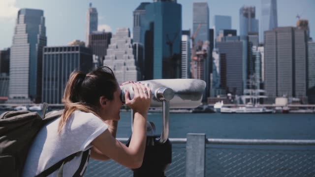 Happy female traveler looks through a tower viewer at epic sunny cityscape skyline of Manhattan, New York slow motion