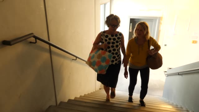 Happy females climbing stairs of dance class Handheld shot of excited female climbing stairs. Mature women are talking while going to dance class. They are wearing casuals. staircases stock videos & royalty-free footage