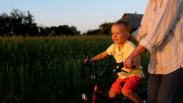 Happy first ride of little boy on bike with granny