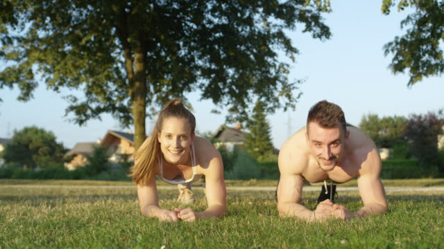 PORTRAIT: Happy fit couple high fives while working out in the sunny nature.