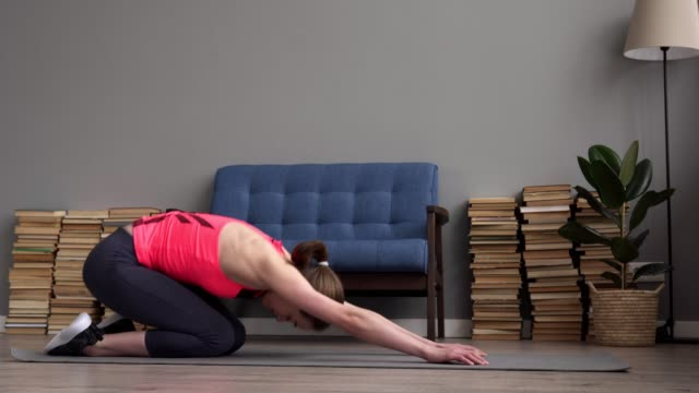 Happy fitness woman doing stretching and relaxation exercises on floor video