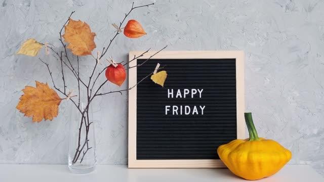 검은 편지 보드에 해피 프라이데이 텍스트와 엽서, 인사말 카드 개념 안녕하세요 가을 금요일 에 테이블 템플릿에 꽃병에 옷핀에 노란색 잎과 가지의 꽃다발 - black friday 스톡 비디오 및 b-롤 화면