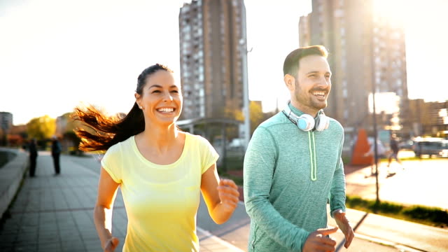 vídeos de stock e filmes b-roll de happy friends and sports people jogging and running outdoor - young woman running city