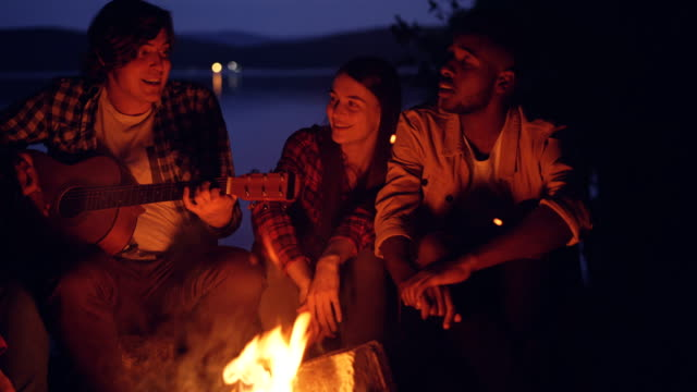 Happy friends are singing and playing the guitar getting warm around fire in forest near river on summer night. Millennials are wearing casual clothing. video
