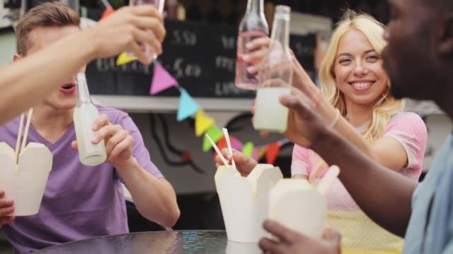 stockvideo's en b-roll-footage met happy vrienden rammelende flessen op food truck - foodtruck