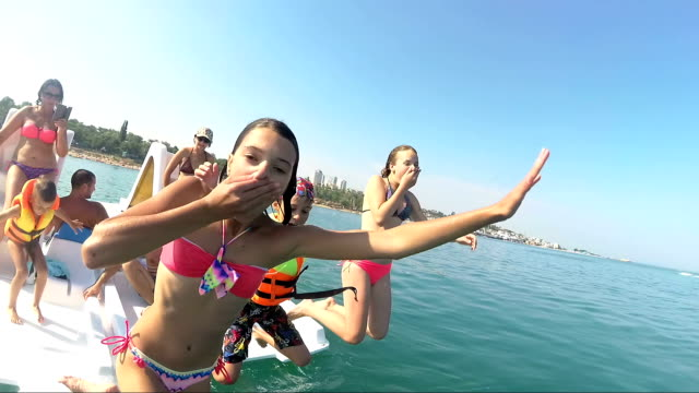 happy friends diving from sailing boat into the sea - young people jumping inside ocean in summer excursion day - nuoto mare video stock e b–roll