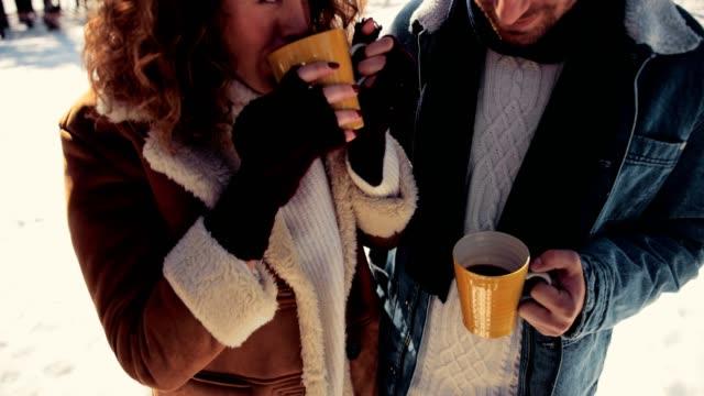 vídeos de stock, filmes e b-roll de amigos felizes bebendo café em dia de neve no inverno - chocolate quente