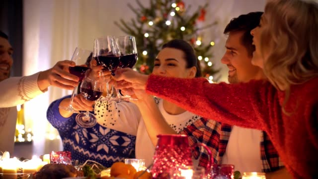 happy friends drinking red wine at christmas dinner - cena natale video stock e b–roll