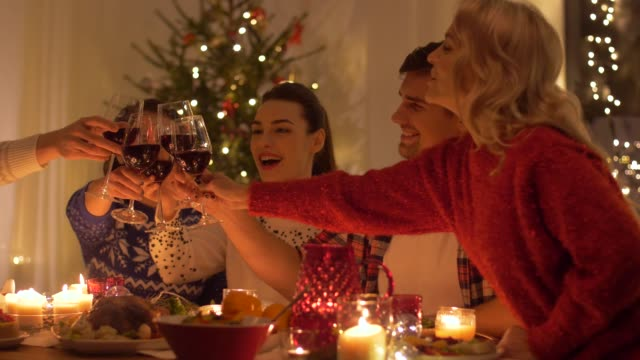 happy friends drinking red wine at christmas - cena natale video stock e b–roll