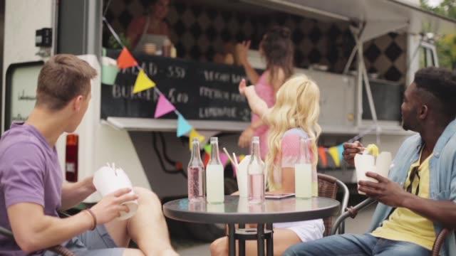 stockvideo's en b-roll-footage met happy vrienden eten en bestellen van voedsel vrachtwagen - foodtruck