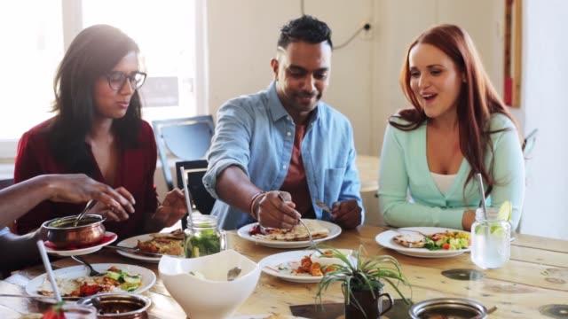 glada vänner äter och talar på restaurang - konserveringsburk bildbanksvideor och videomaterial från bakom kulisserna
