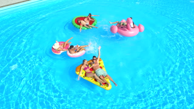 vídeos de stock e filmes b-roll de aerial happy friends having fun and splashing water on colorful floaties in pool - brinquedos na piscina