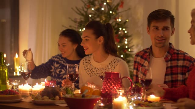 happy friends having home christmas dinner party - cena natale video stock e b–roll