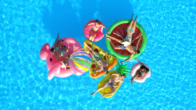 AERIAL Happy friends playing volleyball on fun inflatable floaties in pool water AERIAL TOP DOWN Cheerful girls and guys playing with ball on colourful floaties in pool. Smiling friends enjoying summer vacation on inflatable pineapple, pizza, flamingo, watermelon, doughnut floats floating on water stock videos & royalty-free footage