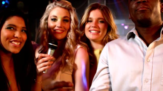 Happy friends singing at the karaoke in night club video