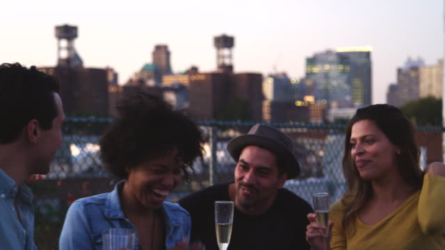 happy friends talk and drink at a table on brooklyn rooftop - alchol video stock e b–roll