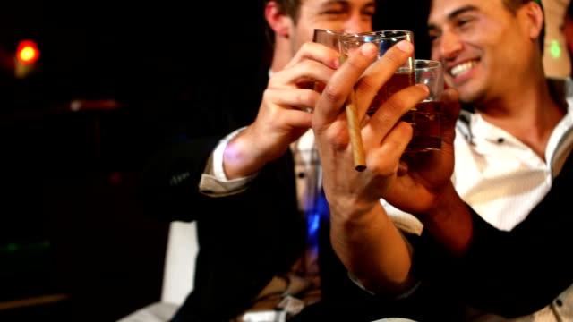 felici amici brindando con un bicchiere di whisky - whisky video stock e b–roll