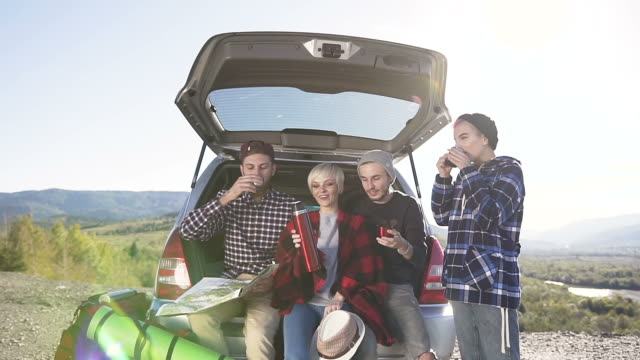 Happy friends traveling in autumn mountains drinking hot tea leaning on the trunk car suv, talking and laughing. Drive by car in the mountains, travel, tourists