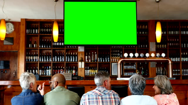 Happy friends watching television in bar 4k Group of happy friends watching television in bar 4k bar counter stock videos & royalty-free footage