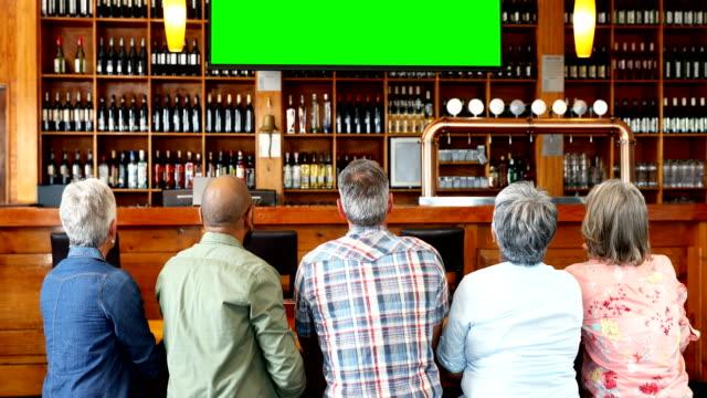 vídeos de stock e filmes b-roll de happy friends watching television in bar 4k - bar local de entretenimento
