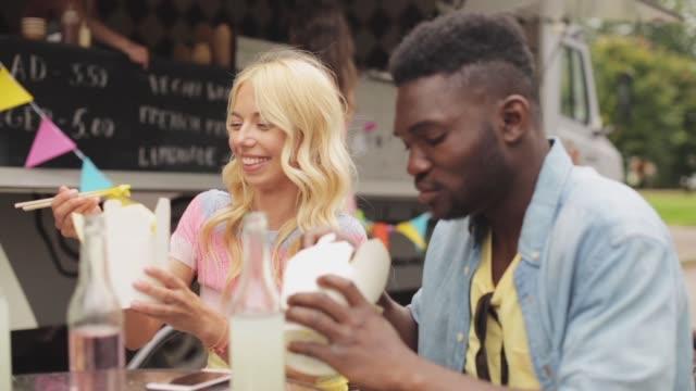 stockvideo's en b-roll-footage met gelukkige vrienden met dranken wok eten bij voedsel vrachtwagen - foodtruck