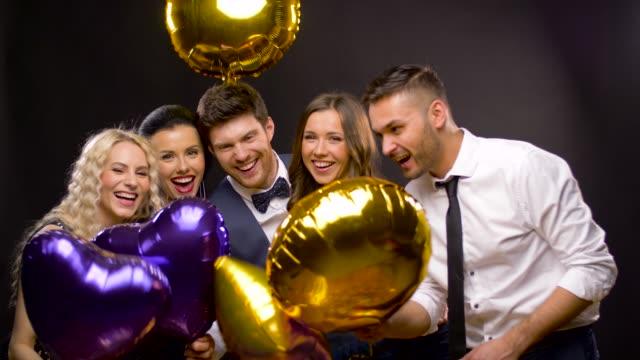 vídeos de stock, filmes e b-roll de amigos felizes com balões dourados e violetas - sul europeu