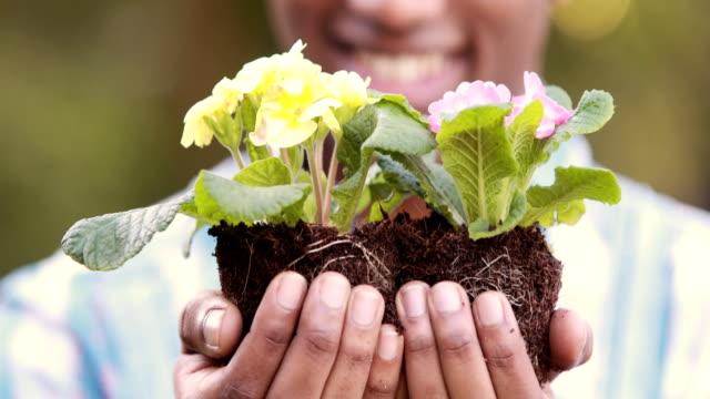 Happy gardener holding a plant video