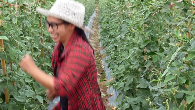 Happy gardeners women dancing in the farmland and smiling to camera. Agriculture and cultivation concept.