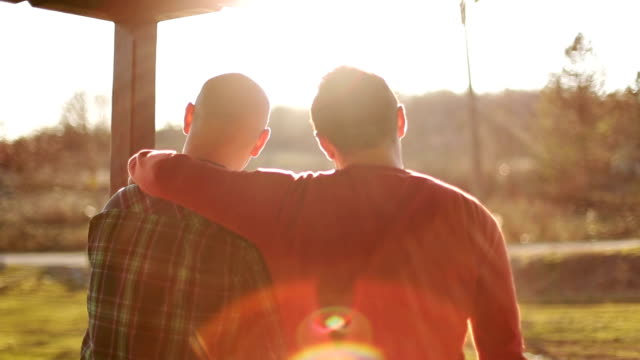 happy gay couple watching sunset video