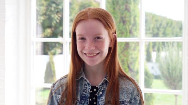 happy ginger teenage girl with freckles smiling against white window - rude włosy filmów i materiałów b-roll