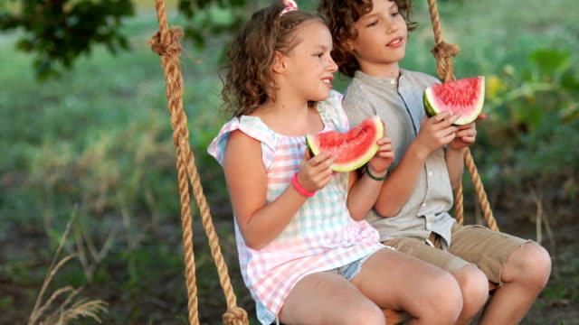 Happy girl and boy eating a watermelon sitting on a swing, summer photo. Children with a watermelon Happy girl and boy eating a watermelon sitting on a swing, summer photo. Children with a watermelon watermelon stock videos & royalty-free footage