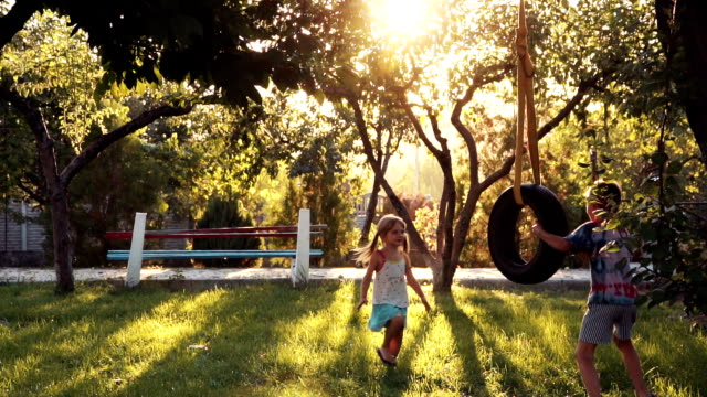 Happy girl and boy playing at park with swing - vídeo