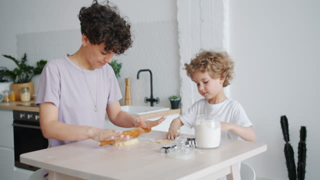 Happy girl and little son rolling dough making cookies at home in kitchen