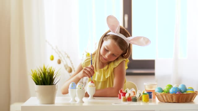 happy girl coloring easter eggs at home - аксессуар для волос стоковые видео и кадры b-roll