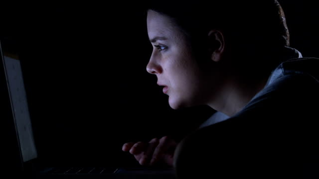 Happy girl communicating with friends in social networks at night, addiction