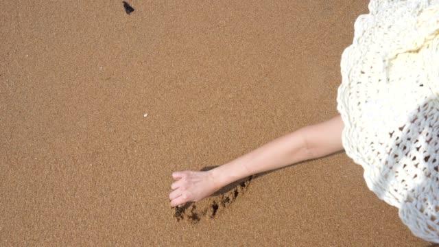 Happy girl draws a heart on a sandy beach