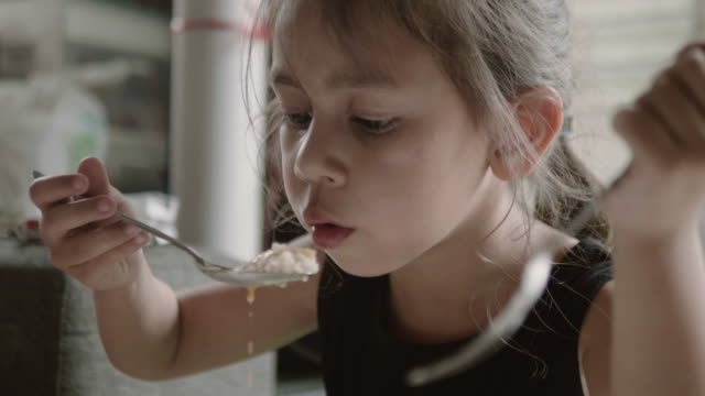 Happy girl eating delicious food with spoon. A little girl eating food at home in morning. Bangkok, Thailand. rice cereal plant stock videos & royalty-free footage