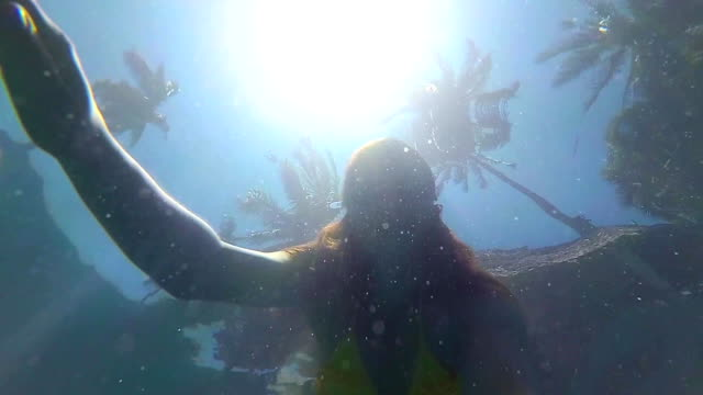 happy girl happy swims underwater in the pool. sunlight through the water - solo bambini maschi video stock e b–roll