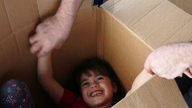 glad tjej gömma sig inuti en stor kartong som flyttar till ett nytt hus - flyttlådor bildbanksvideor och videomaterial från bakom kulisserna