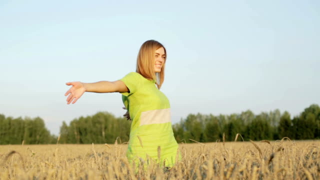 Happy girl in a green dress is waving her hands standing among ripe ears of wheat. video
