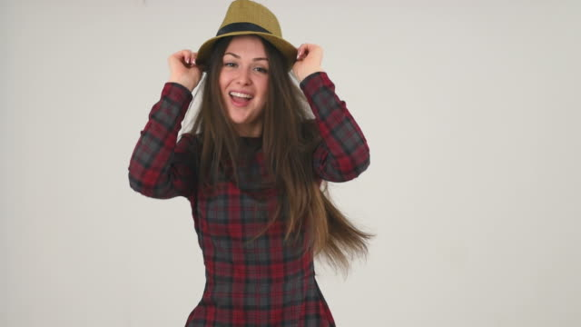 Happy girl in hat dancing Happy girl in hat dancing on grey background, slow motion arms akimbo stock videos & royalty-free footage