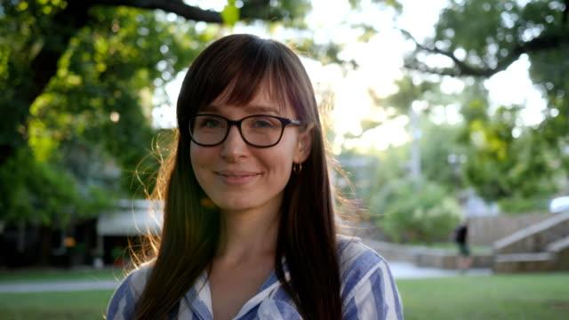 glückliches mädchen in stilvolle brillen lächelt in die kamera im park am hintergrund bäume - brille stock-videos und b-roll-filmmaterial