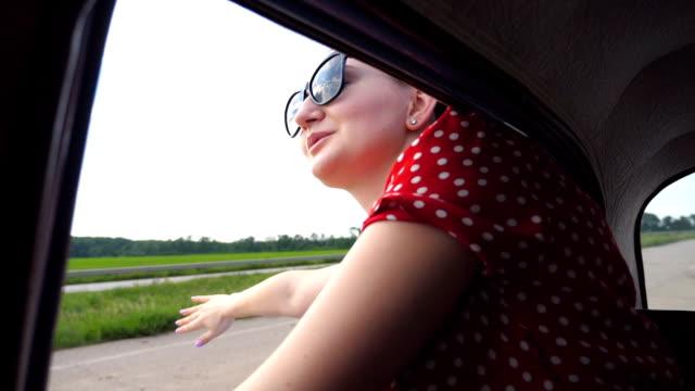 ragazza felice con occhiali da sole appoggiata fuori dal finestrino dell'auto retrò e godendosi il viaggio. attraente giovane donna che cerca di spostare auto vintage il giorno d'estate. concetto di viaggio e libertà. primo piano al rallentatore - braccio umano video stock e b–roll