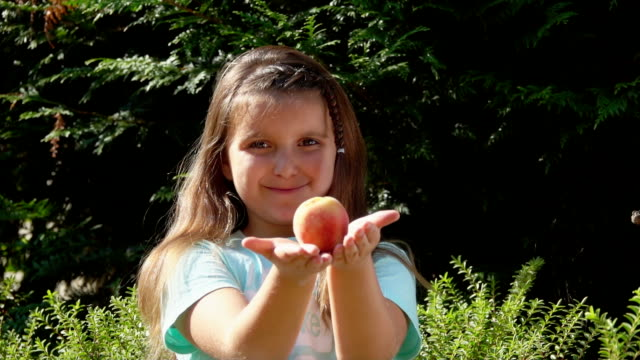 happy girl is eating a delicious ripe peach outdoors - pesche bambino video stock e b–roll