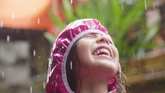 vídeos de stock e filmes b-roll de a happy girl is playing in the rain and is happy because she has fun. - chapéu