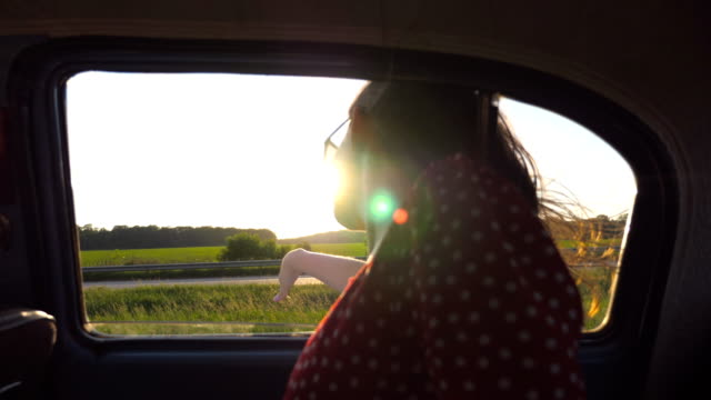 happy girl leaning out of retro car window and playing with wind. young woman waving with her hand in wind at travel. female tourist looking out the window of old car to feel the breeze. slow motion - viaggio in macchina video stock e b–roll
