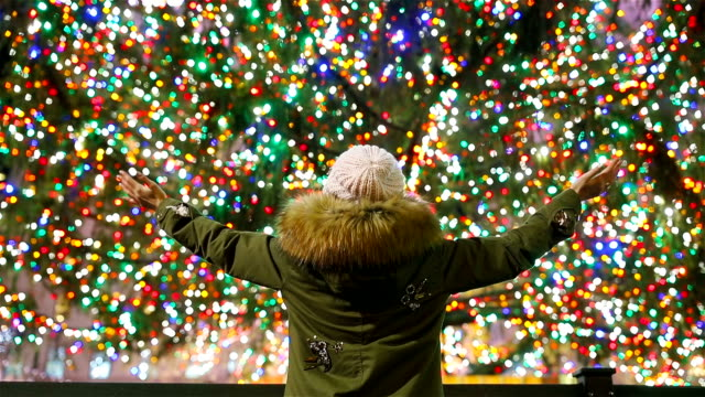 Happy girl on the background of the Rockefeller Christmas tree in New York. Beautiful Christmas Tree at Rockefeller center Happy girl on the background of the Rockefeller Christmas tree in New York christmas fun stock videos & royalty-free footage